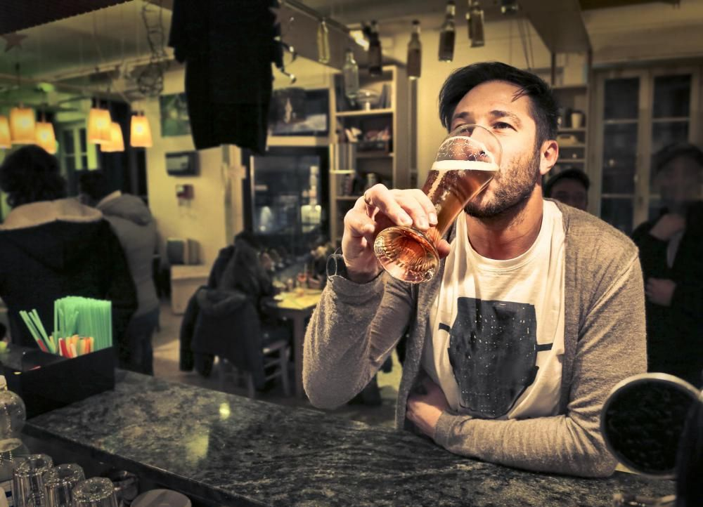 man-in-bar-drinking-glass-of-beer